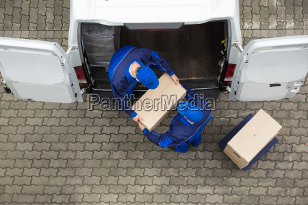 two delivery men unloading cardboard box