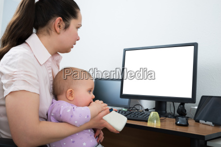 woman with her baby using computer