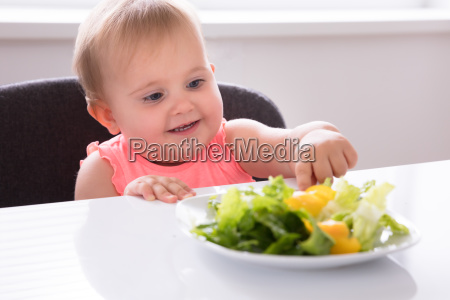baby girl eating vegetable