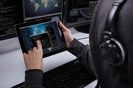 hacker using digital tablet for stealing