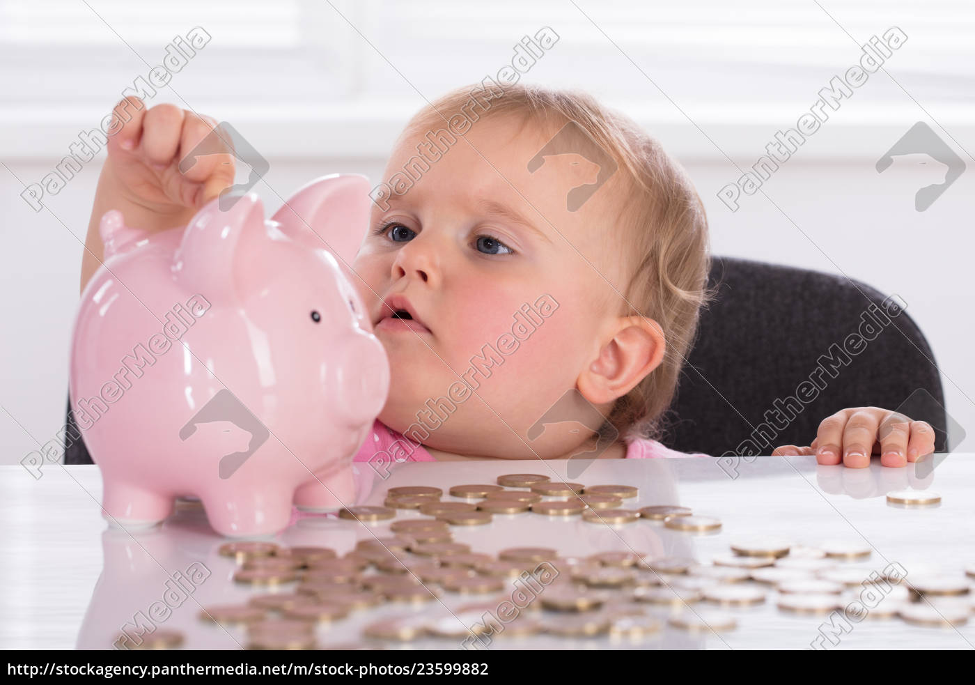 baby, inserting, coin, in, piggybank - 23599882