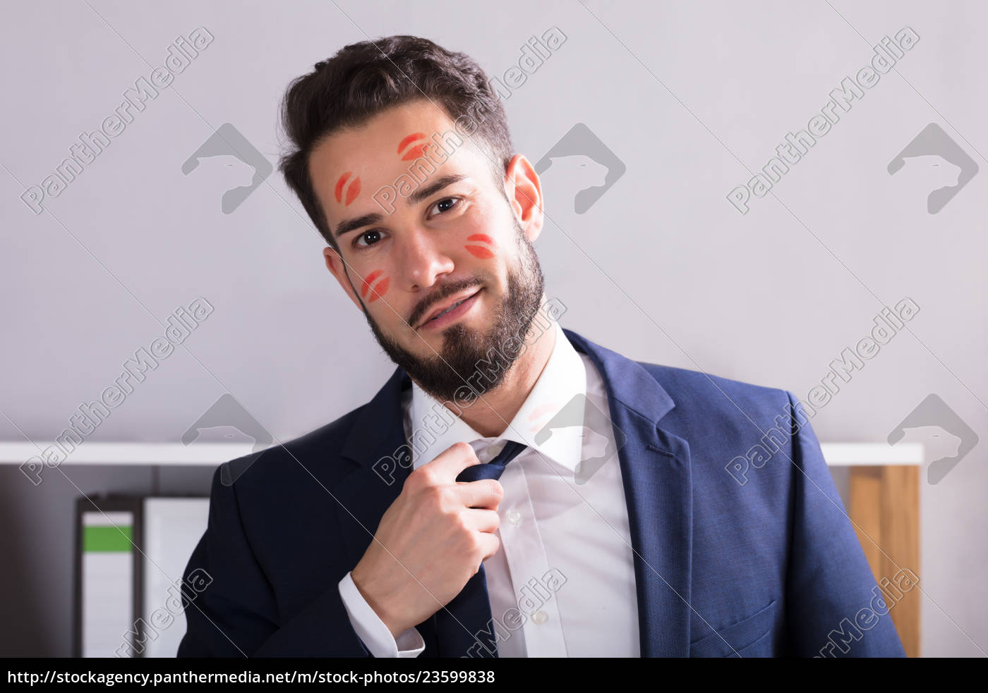 businessman, with, lipstick, kiss, marks, on - 23599838