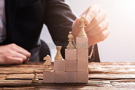 businessperson, arranging, chess, piece, on, wooden - 23599980