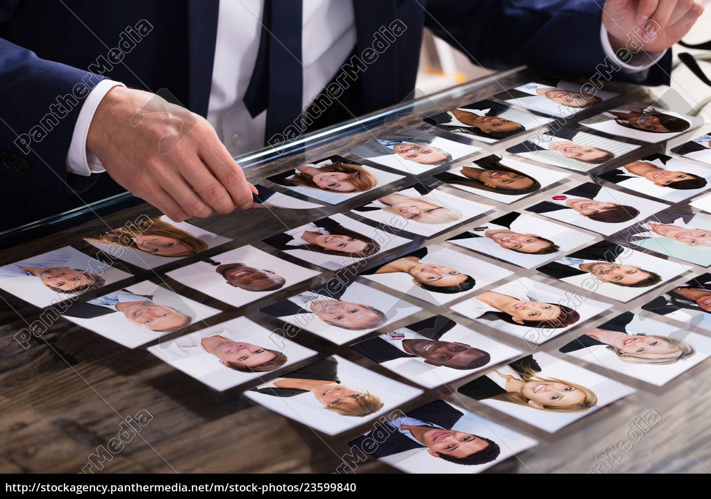 businessperson, choosing, photograph, of, candidate - 23599840