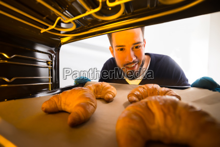 man, taking, out, tray, of, croissants - 23599748