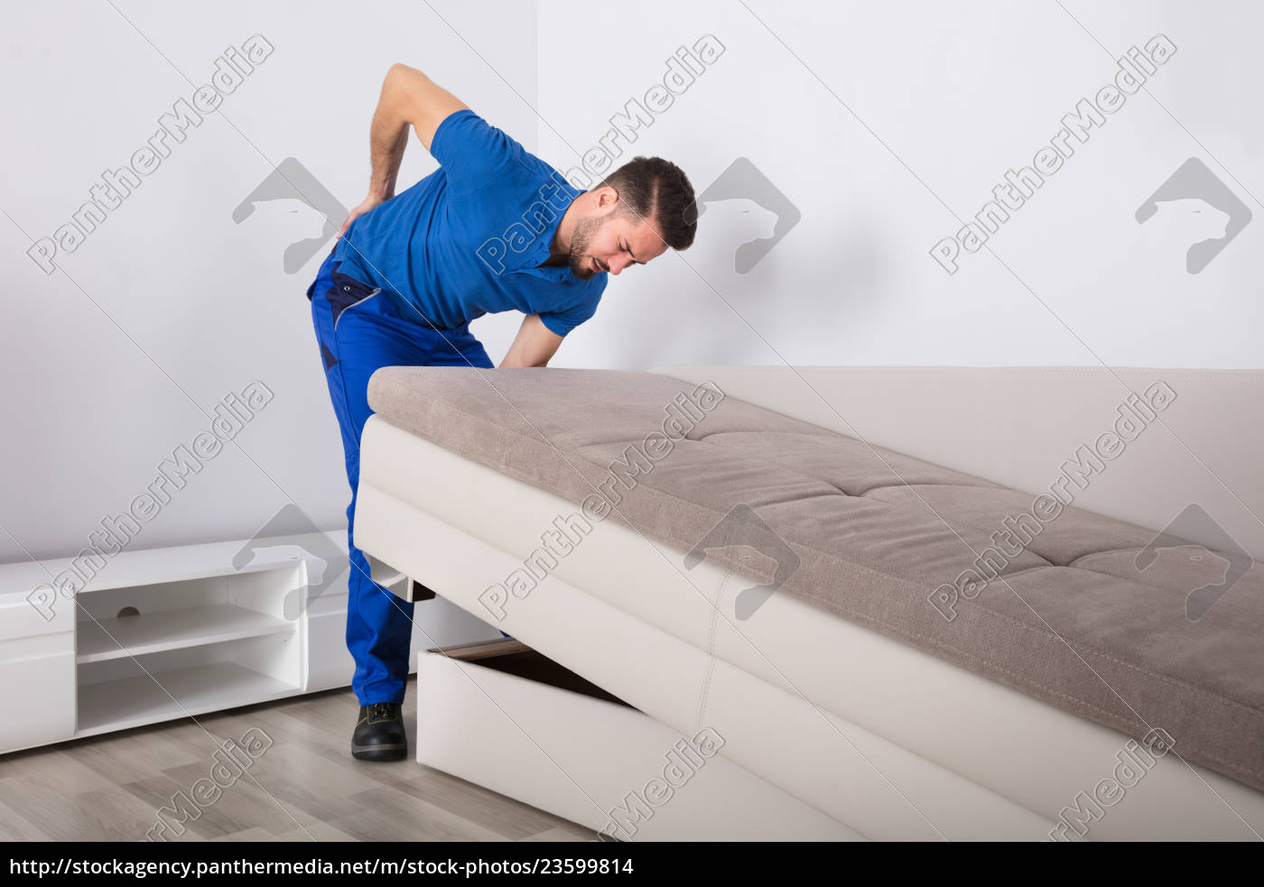 mover, suffering, from, backpain, while, lifting - 23599814
