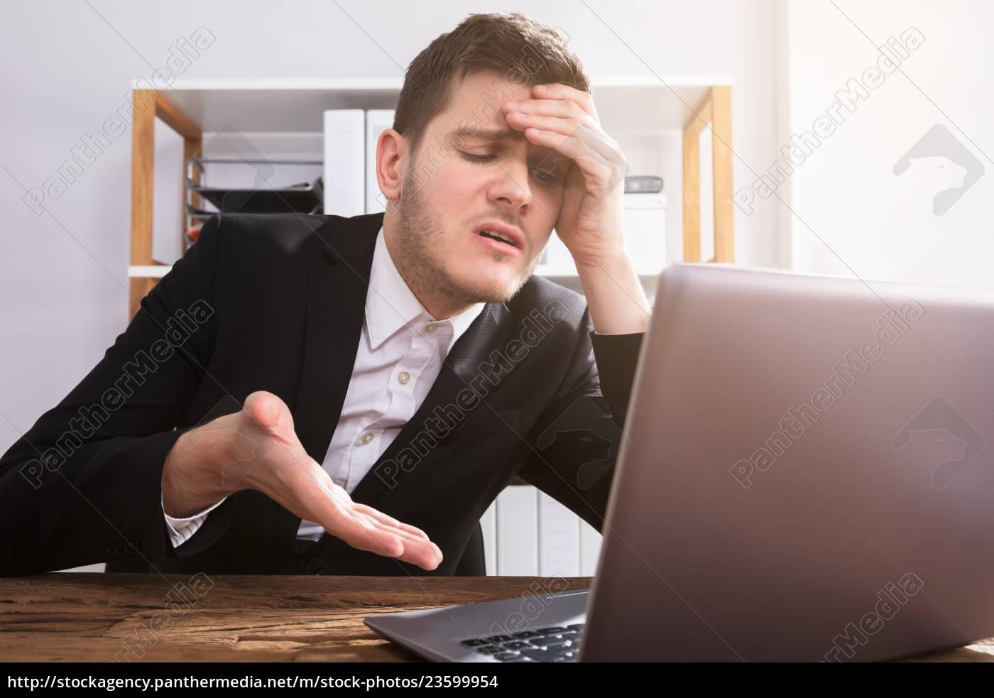 sad, businessman, looking, at, laptop - 23599954