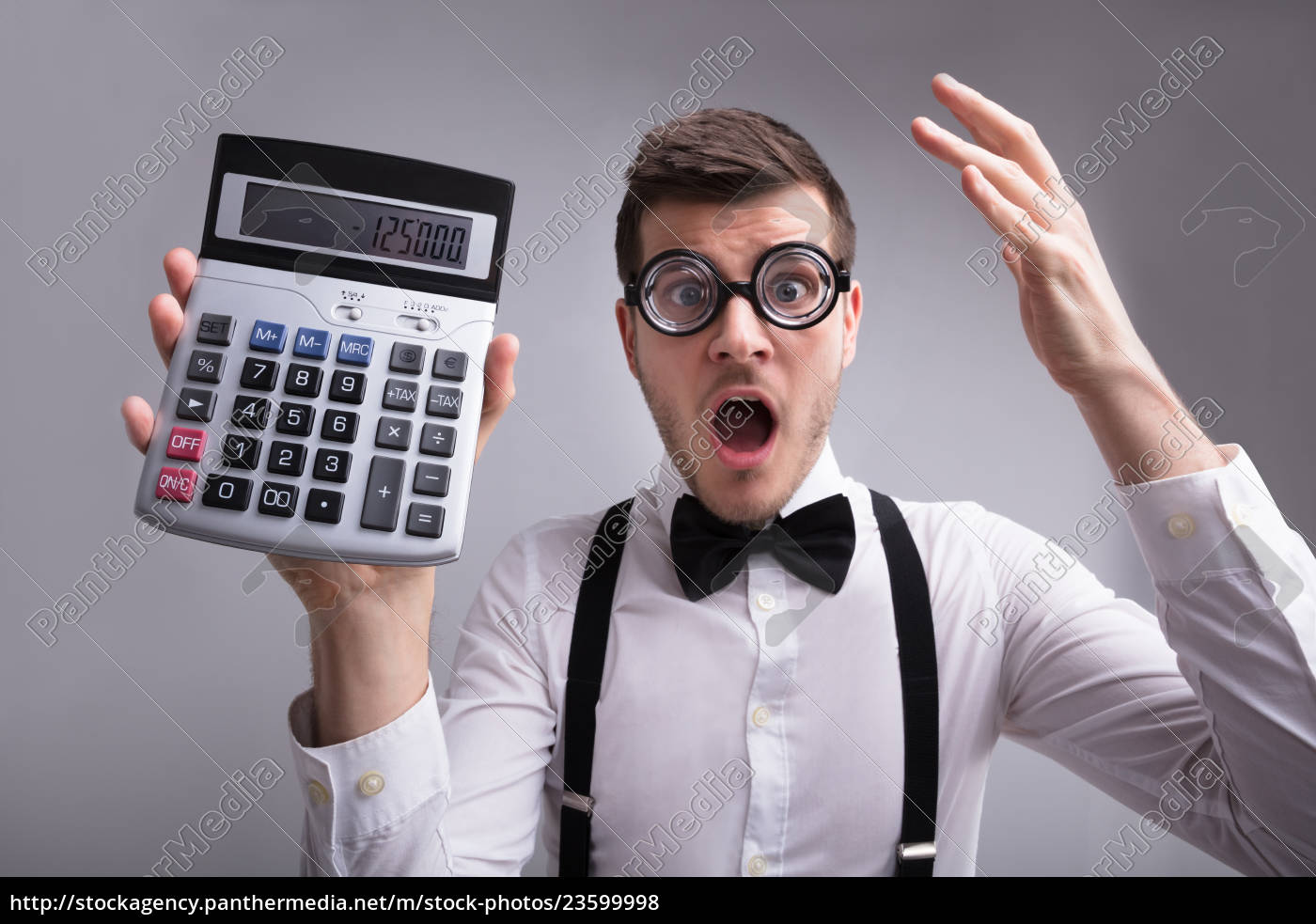 shocked, young, man, holding, calculator - 23599998