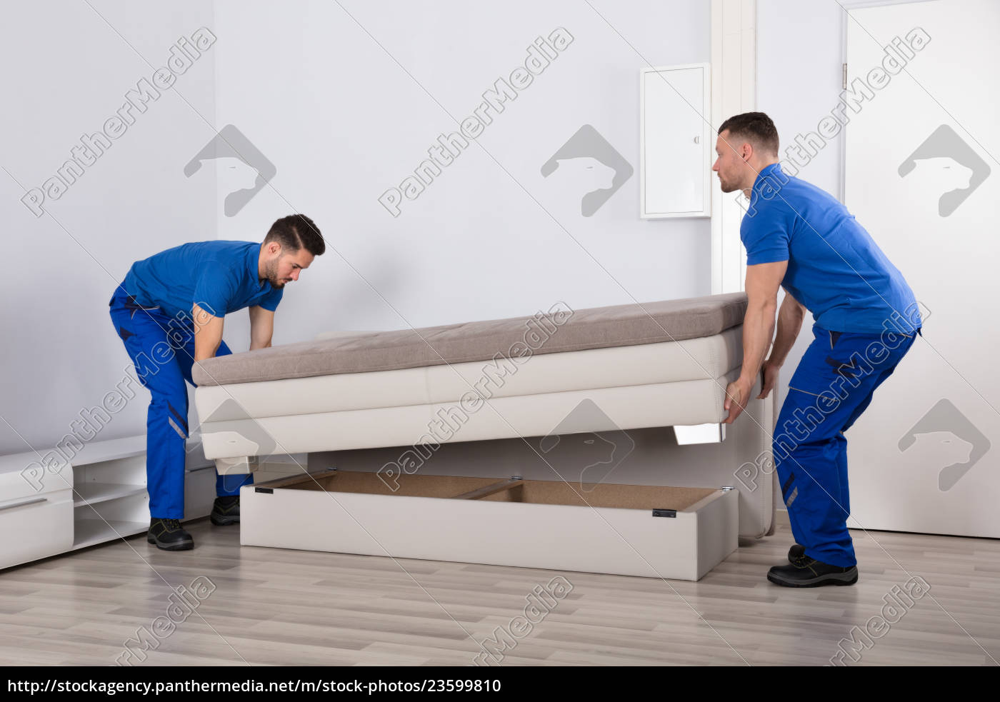 two, men, holding, sofa, in, living - 23599810