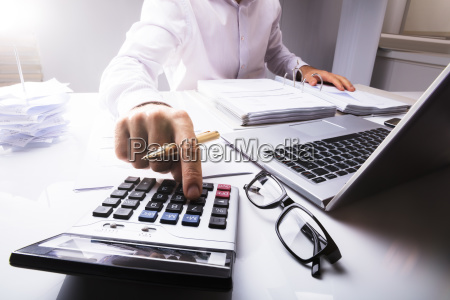 businessman calculating tax using calculator