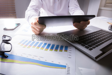 businessman using digital tablet with graph