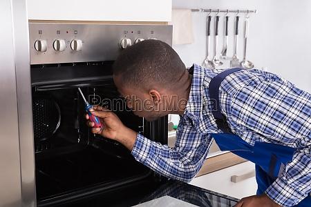 repairman fixing kitchen oven