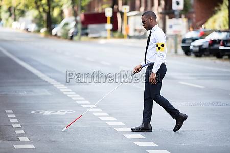 blind man wearing armband walking with
