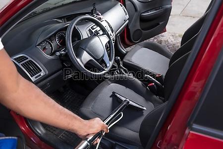 worker vacuuming car interior