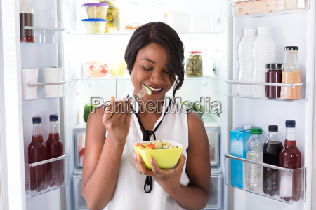 african, woman, eating, fruits, in, bowl - 23600620