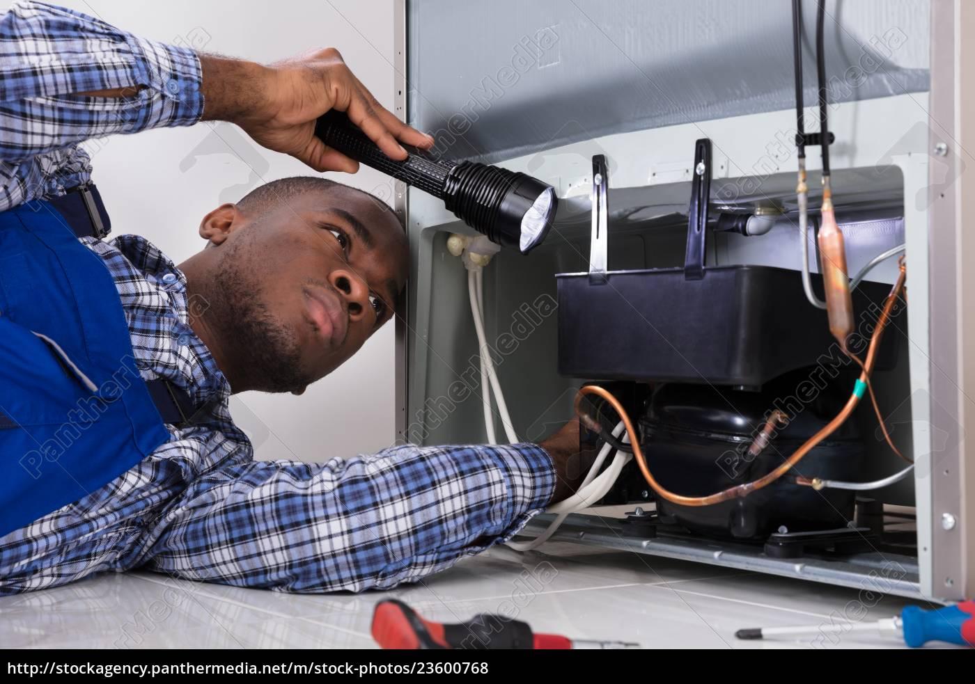 handyman, checking, refrigerator, with, flashlight - 23600768