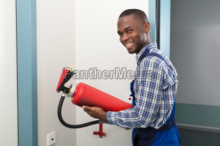 male, african, professional, holding, fire, extinguisher - 23600788