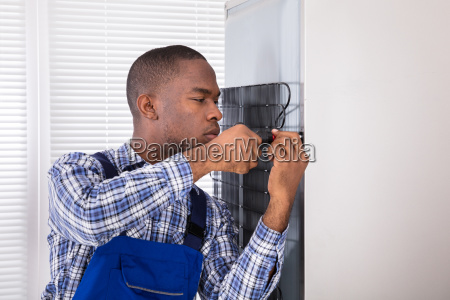 serviceman, in, overall, working, on, fridge - 23600740