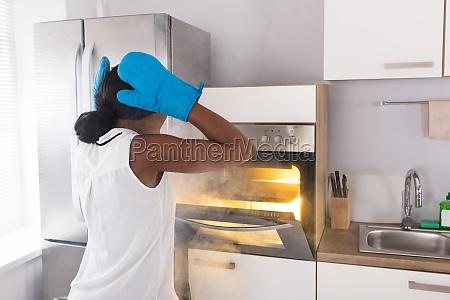 shocked, woman, looking, at, burnt, cookies - 23600612