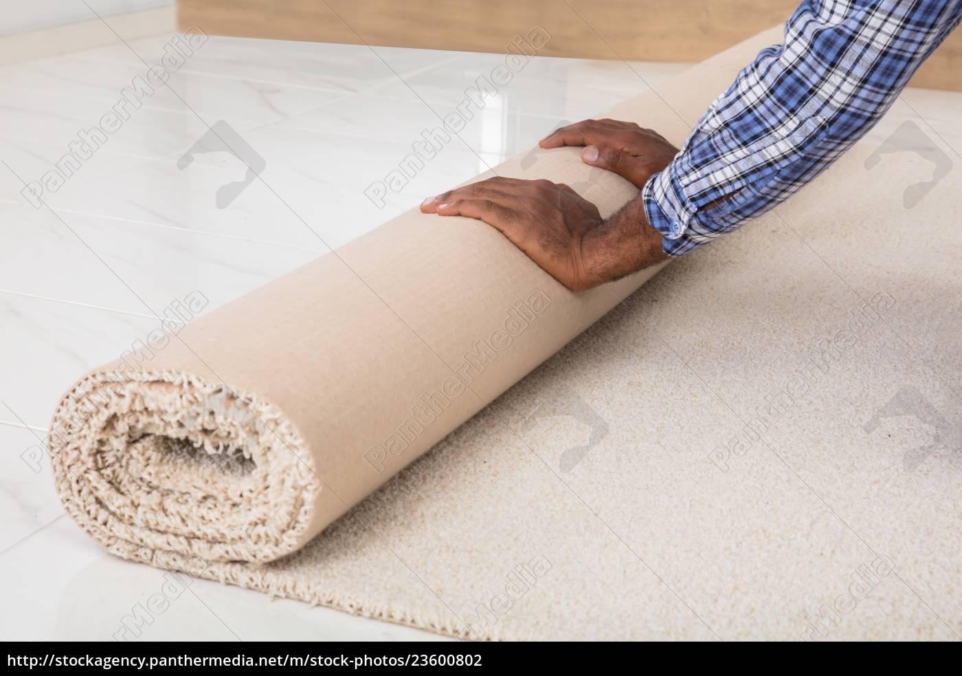 worker's, hands, rolling, carpet - 23600802