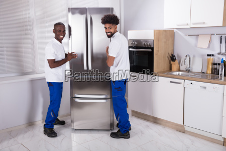 two male movers fixing the freezer
