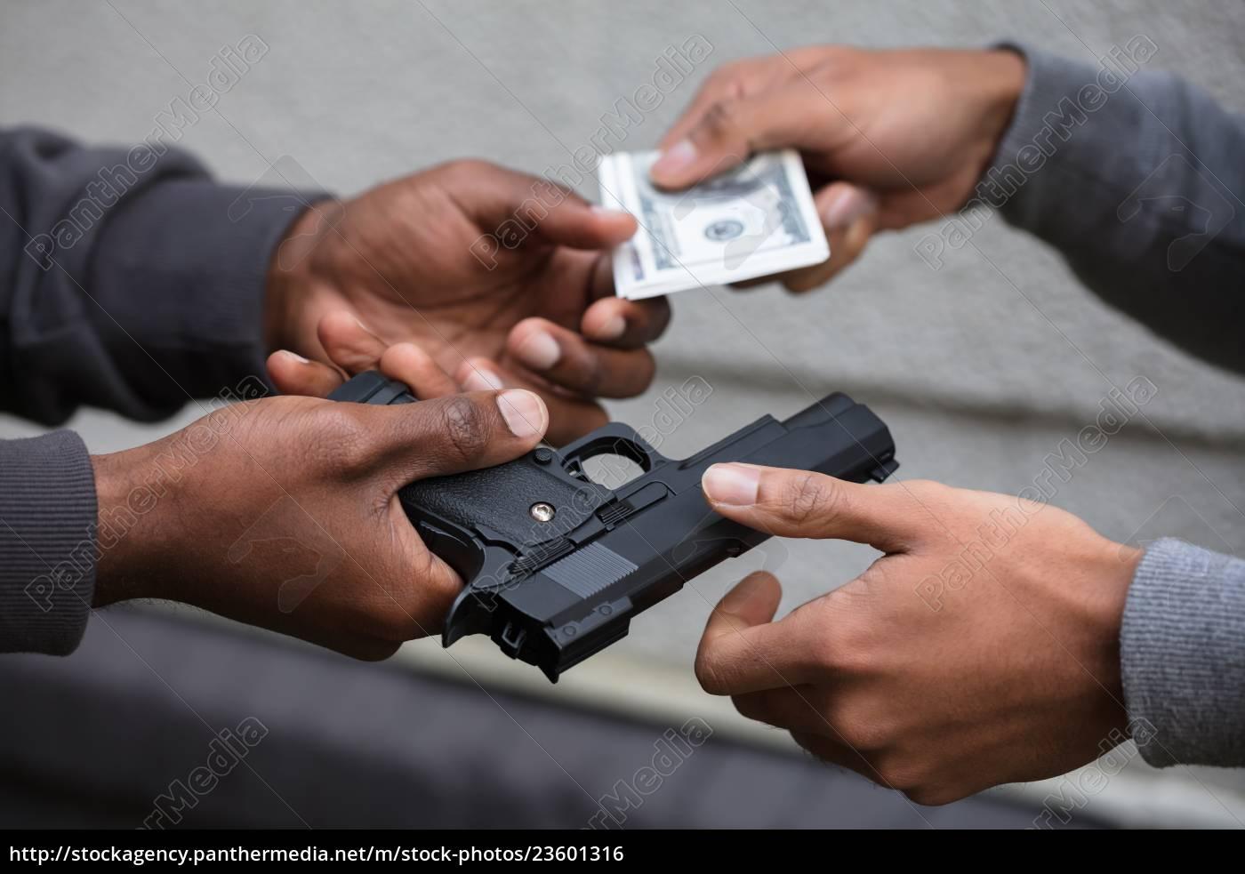 hands, exchanging, handgun, for, banknote - 23601316