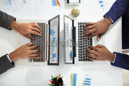 two, businesspeople, analyzing, graph, on, laptop - 23601272
