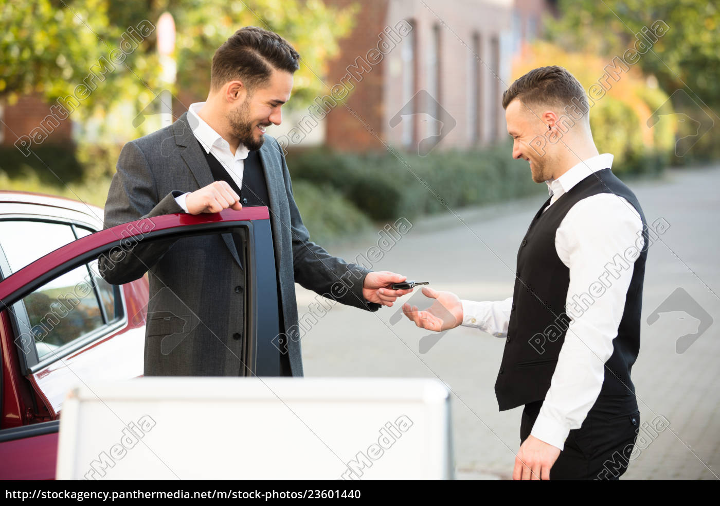 young, businessman, giving, car, key, to - 23601440