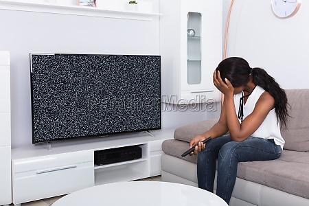 woman sitting on sofa near television