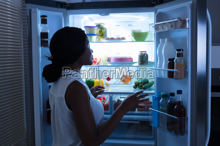 woman taking out bottle from refrigerator