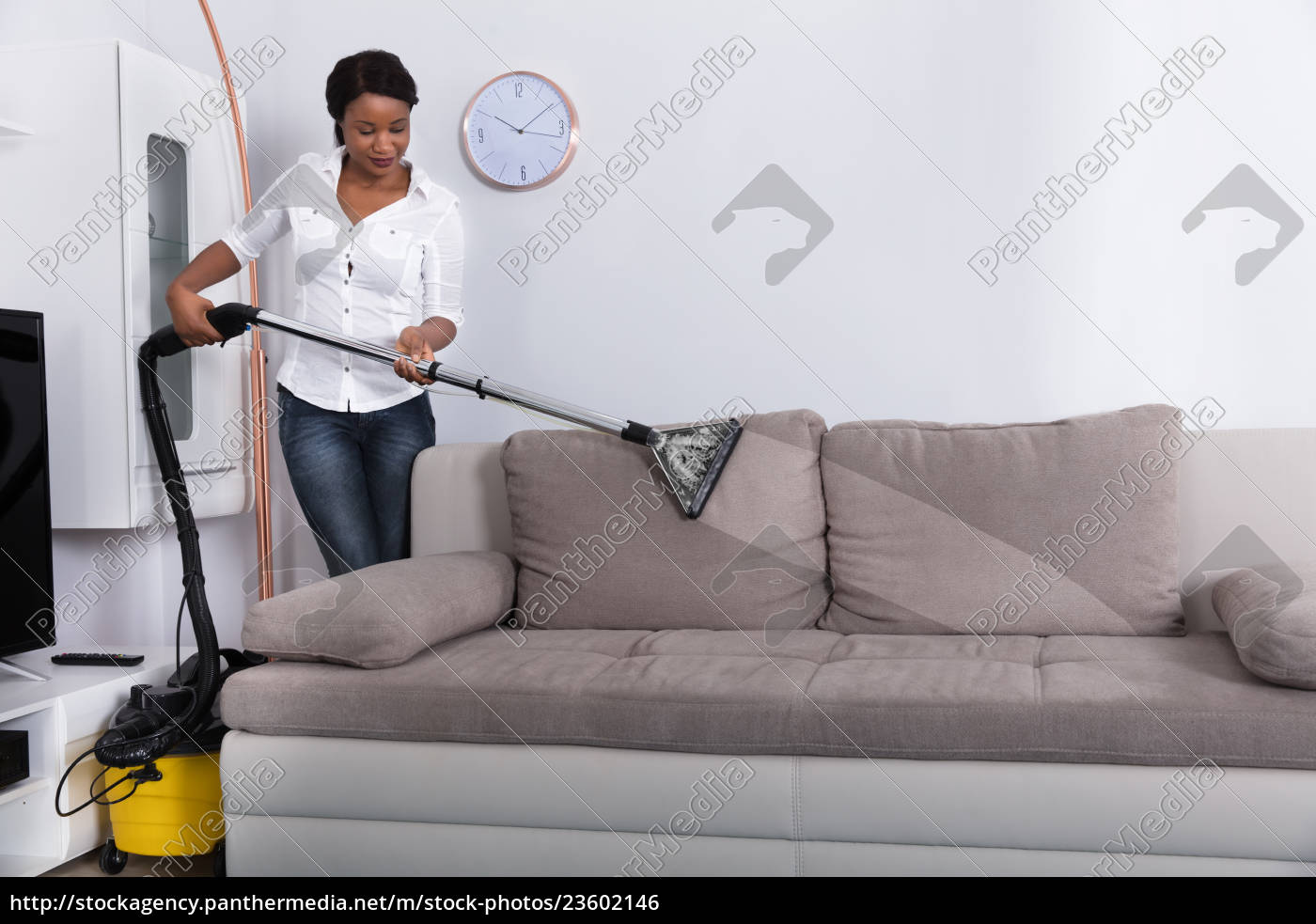 african, woman, cleaning, sofa, with, vacuum - 23602146