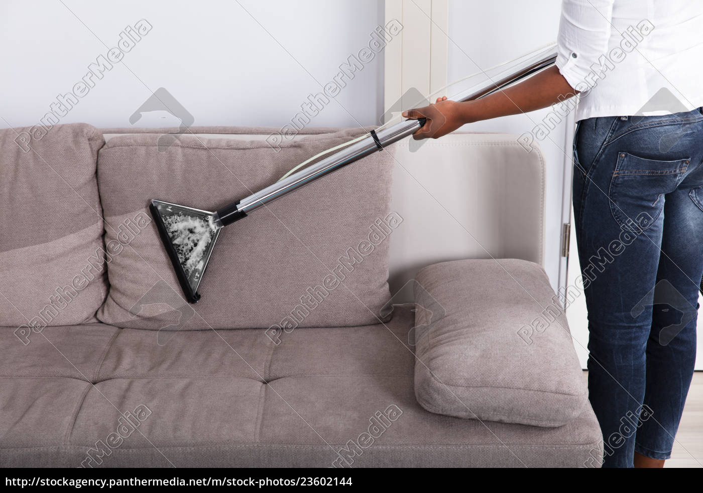 housewife, cleaning, sofa, with, vacuum, cleaner - 23602144