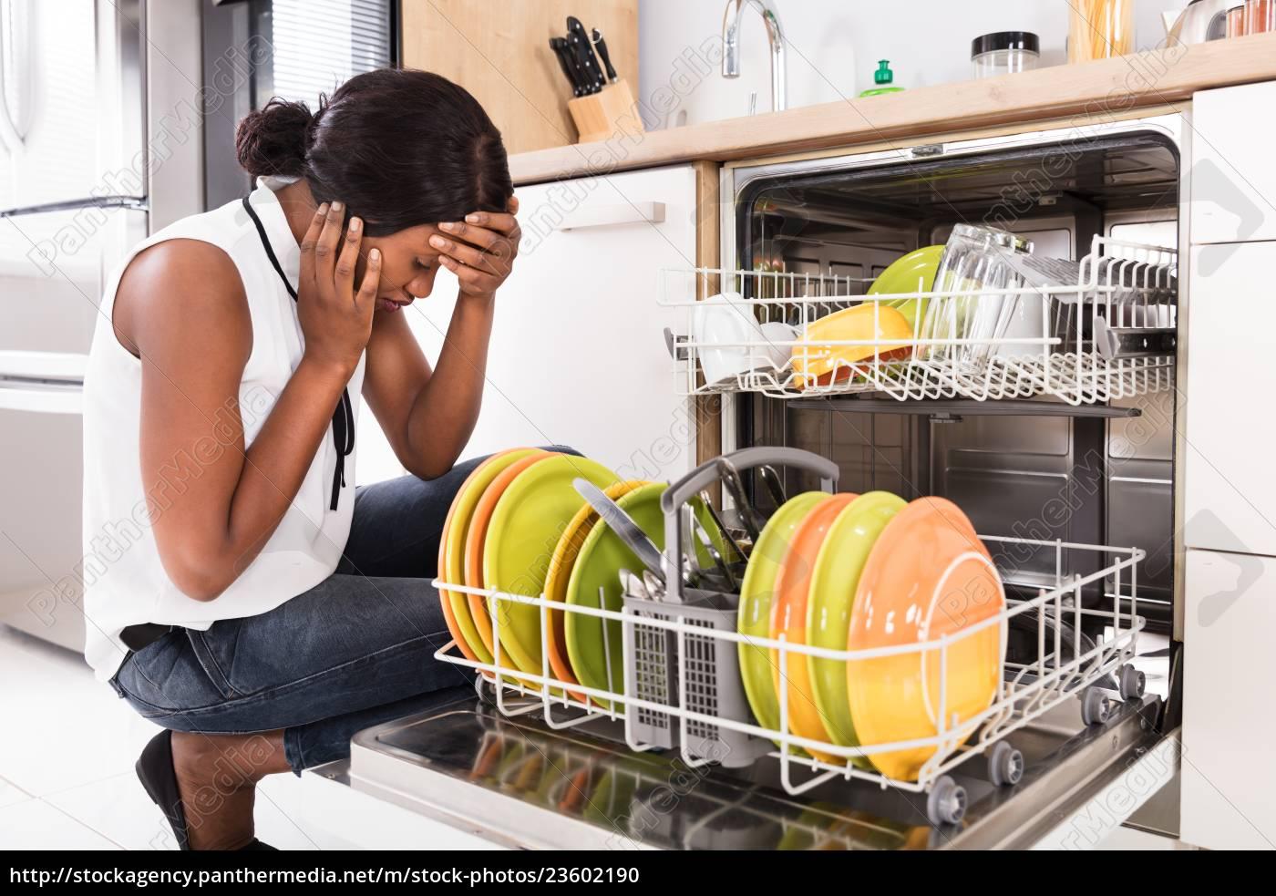 sad, woman, crouching, near, dishwasher - 23602190