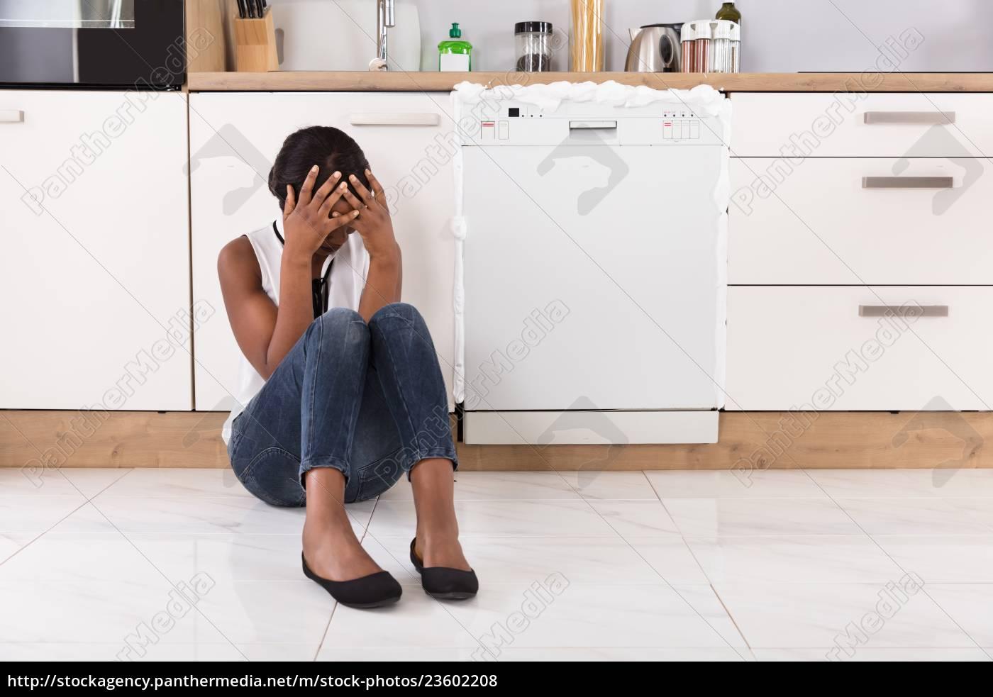 upset, woman, sitting, next, to, dishwasher - 23602208