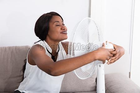 woman, enjoying, breeze, with, electric, fan - 23602210