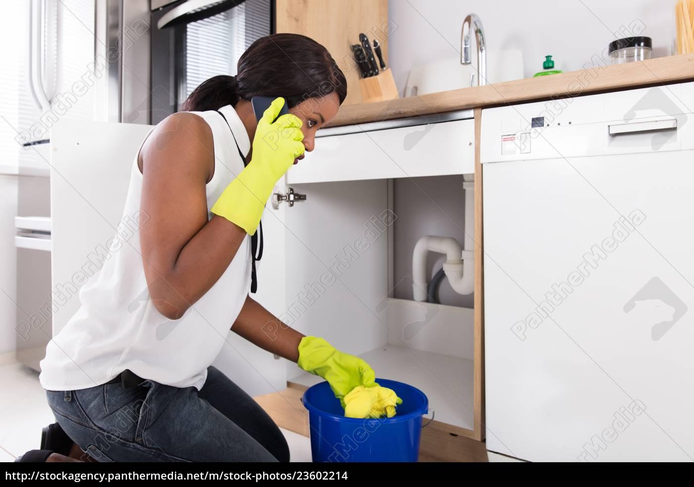 woman, holding, yellow, napkin, calling, plumber - 23602214