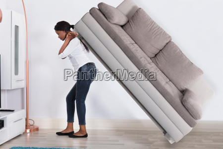 woman, trying, to, move, large, sofa - 23602148