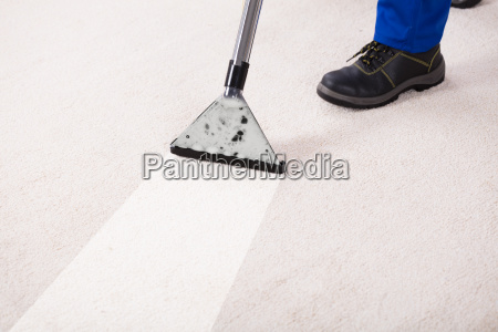 person using vacuum cleaner for cleaning