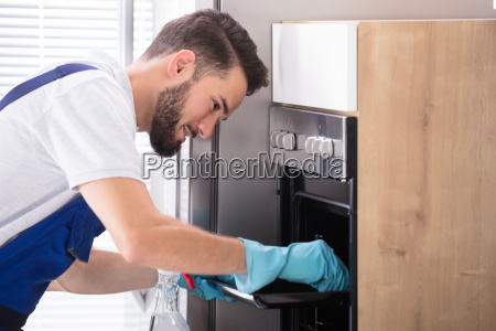 janitor cleaning oven in kitchen