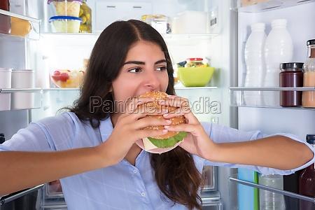 happy, woman, eating, burger - 23603614