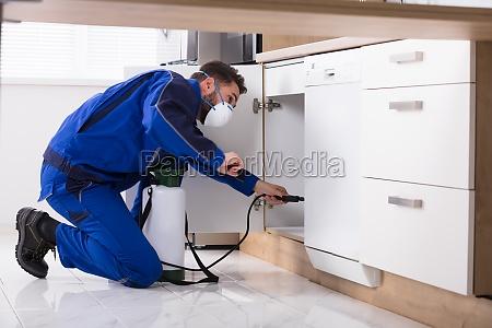 man, spraying, pesticide, in, kitchen - 23603432