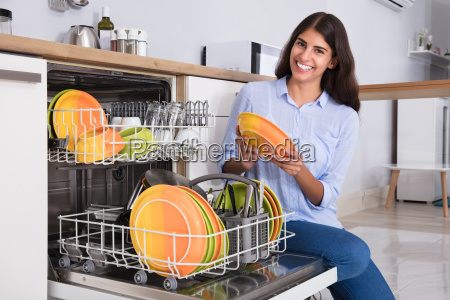 woman, arranging, plates, in, dishwasher - 23603652