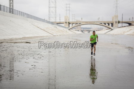 mixed race man running in canal