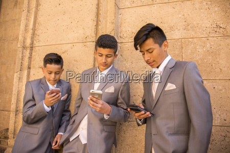 hispanic boys wearing suits texting on
