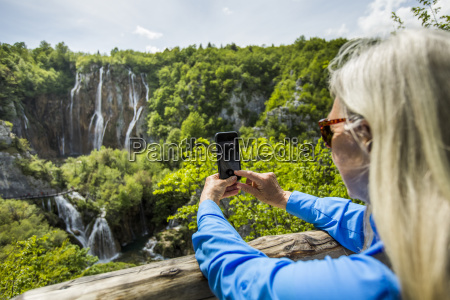 older caucasian woman photographing waterfalls with