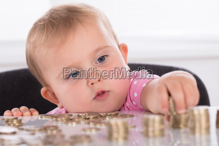 baby stacking coins on desk