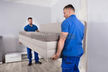 two men holding sofa in living