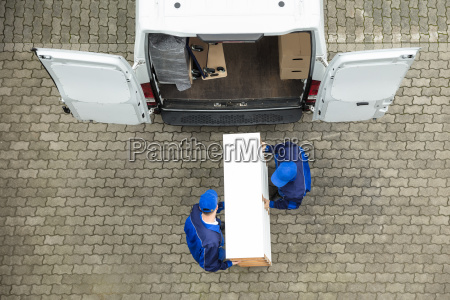 two delivery men unloading furniture from