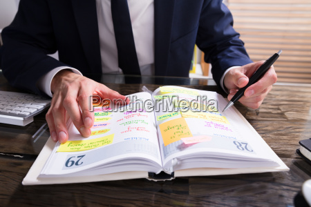 businessperson, writing, schedule, in, diary - 23610424