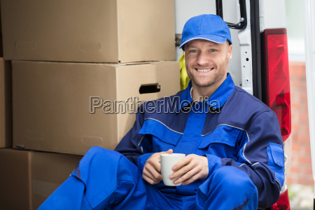 delivery, man, drinking, cup, of, coffee - 23610666